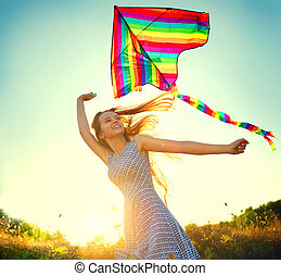 Beauty girl in short dress running with kite on the field