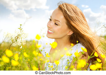 Beauty Girl in the Meadow lying on Green Grass