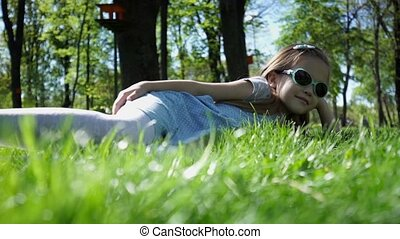 Beauty Girl lying on the Meadow with green grass
