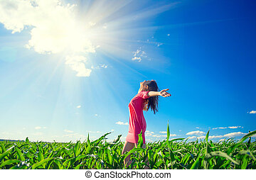 Beauty girl on summer field rising hands over blue clear sky. Happy young healthy woman enjoying nature outdoors