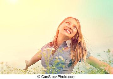 Beauty girl outdoors enjoying nature. Beautiful teenage girl having fun on spring field