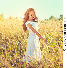 Beauty girl outdoors enjoying nature. Beautiful teenage model girl with perfect long curly hair