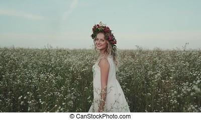 Beauty girl running cross the flower field at sunset