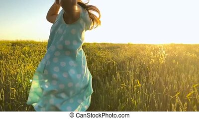 Beauty girl running in a yellow hat on green wheat field over sunset sky. Freedom concept. Wheat field in sunset