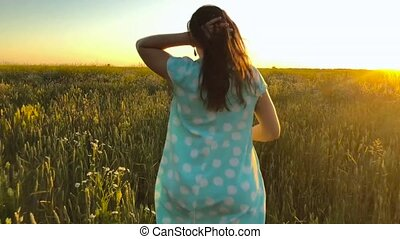 Beauty girl running on green wheat field over sunset sky. Freedom concept. Wheat field in sunset.