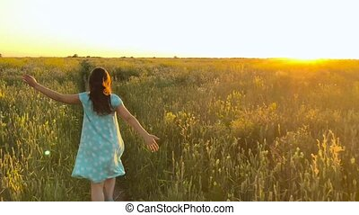 Beauty girl running on green wheat field over sunset sky. Freedom concept. Wheat field in sunset