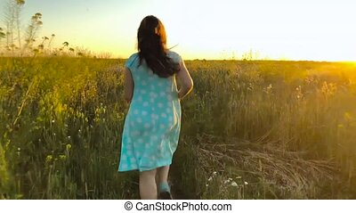 Beauty girl running on green wheat field over sunset sky. Freedom concept. Wheat field in sunset. Slow motion