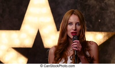 beauty girl singing with a microphone, slow motion, close up
