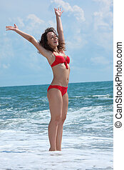 beauty girl stands in sea surf with rised hands