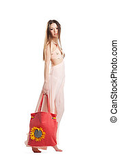 Beauty girl walk in rose dress and red beach bag