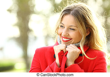 Beauty girl warmly clothed wearing red jacket in winter