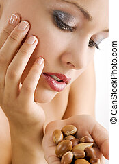 sweet beauty portrait of blond girl looking at some argan seeds on her hand