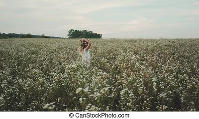 Beauty girl with flower wreath on head running cross the flower field at sunset