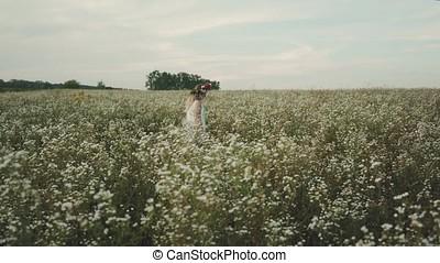 Beauty girl with flower wreath on head running cross the flower field