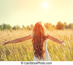 Beauty girl with long hair enjoying nature, raising hands