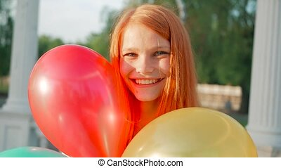 Beauty girl with red hair and colorful air balloons spinning and laughing, on white background. Beautiful Happy Young woman on birthday holiday party. Joyful model having fun, celebrating