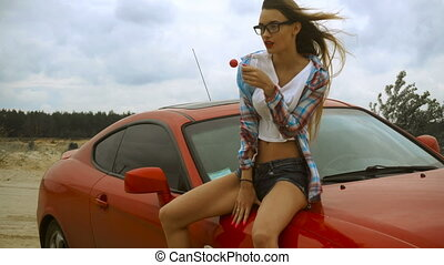 Beauty girl with red lips sits on a car and licks a lollipop
