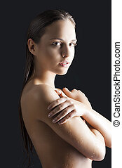 beauty girl with wet skin, she looks in to the lens
