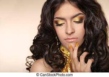 Beauty Golden eye makeup eyeshadow. Brunette woman with curly hair and manicured nails over beige background