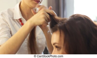 young woman and hairdresser with hair iron making hairdo at...