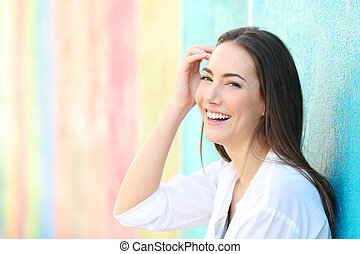Beauty happy woman in a colorful wall looking at camera