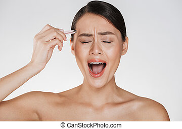 Beauty image of stressed young woman with brown hair screaming in pain while plucking eyebrows using tweezers, isolated over white background