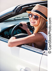 Beauty in convertible. Beautiful young funky woman in sunglasses sitting on front seat of her convertible and smiling