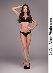 Beauty in lingerie. Full length of beautiful young women in lingerie posing and smiling at camera while standing isolated on grey