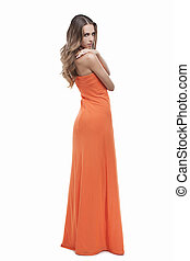 Beauty in orange dress. Full length of attractive young woman in orange dress posing while isolated on white