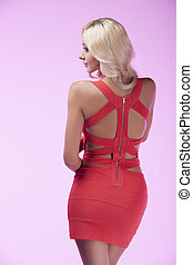 Beauty in red. Rear view of attractive blond hair woman posing while isolated on coloured background