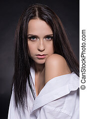 Beauty in shirt. Beautiful young woman in white shirt looking at camera while isolated on grey