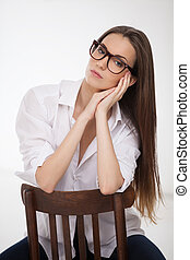 Beauty in shirt. Thoughtful young woman holding her hands clasped and looking at camera while sitting on the chair