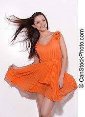 beauty, in, sinaasappel, dress., mooi, jonge vrouw , in, sinaasappel, jurkje, het poseren, en, het glimlachen, vrijstaand, op wit