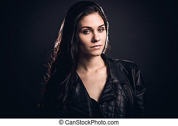 Beauty in style. Beautiful young woman in leather jacket looking at camera while standing against dark grey background