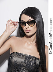 Beauty in sunglasses. Portrait of attractive young woman in sunglasses looking at camera while isolated on white