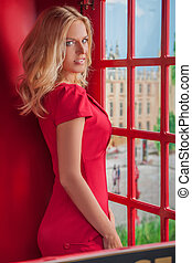 Beauty in telephone booth. Attractive young blond hair woman in red smiling while standing in telephone booth