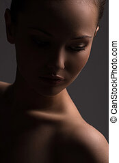 Beauty in the dark. Portrait of beautiful young naked woman looking away while isolated on grey