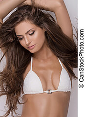 Beauty in white bra. Portrait of attractive young woman in white bra looking away and posing while isolated on grey