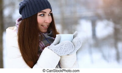 Beauty Joyful Model Girl holding cup with hot tea and smiling, having fun in winter park. Beautiful young woman laughing outdoors. Enjoying nature, wintertime