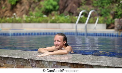 Beauty Leaning on Poolside - Attractive young woman leaning...