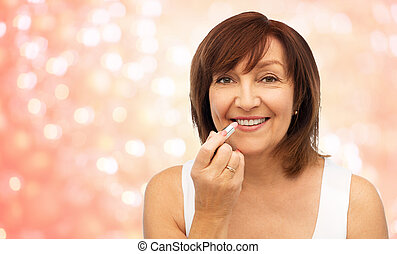 smiling senior woman applying lipstick to her lips