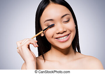 Beauty make-up. Beautiful young and shirtless Asian woman holding make-up brush and smiling while standing against grey background