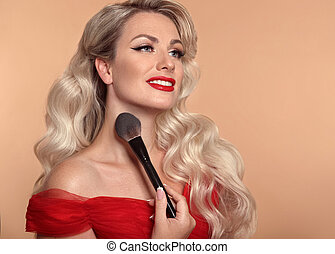Beauty makeup. Fashion glamour portrait of happy smiling blonde woman with red lips and long wavy hair style holding brush over beige studio background. Beautiful face Make up product cosmetics.