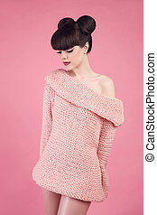 Beauty makeup. Fashion teen girl model. Brunette with matte lips and hairstyle wearing wool sweater posing over studio pink background.