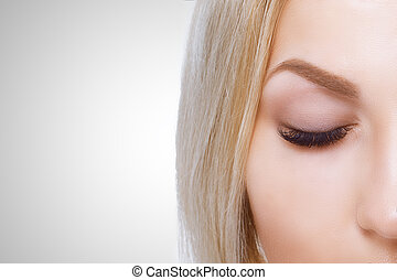 Beauty makeup for blue eyes. Part of beautiful face closeup. Perfect skin, long eyelashes, make up concept.