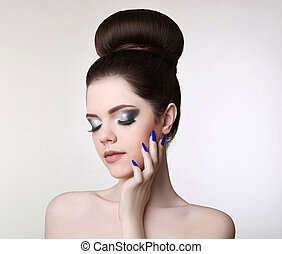 Beauty makeup girl. Fashion bun hairstyle. Manicure nail. Young fresh brunette with natural matte lipstick and glitter eyeshadow isolated on studio background.