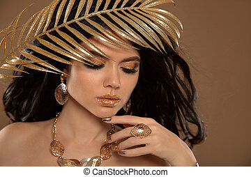 Beauty makeup in gold. Fashion brunette girl with Long wavy hair, luxury jewelry and golden art nail manicure. Beautiful tanned sexy woman posing over beige studio background.
