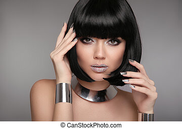 Beauty Makeup, Silver Manicured polish nails. Bob hairstyle. Fashion Style Brunette Woman Portrait with black Short Hair and glitter lips isolated on gray background. Jewelry set.