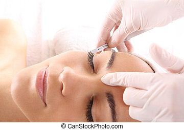Cutting scars woman during treatment with dermatologist