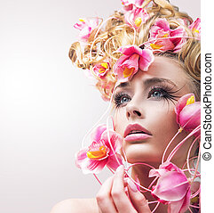 Beauty model girl with beautiful flowers in her hair